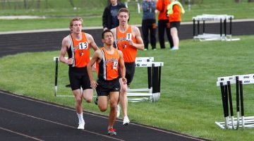 Shawn Bell (left) and Daniel Steele (right) help push teammate Abdiel Cardiel to a personal best in the 800 meters. | Scott Rains